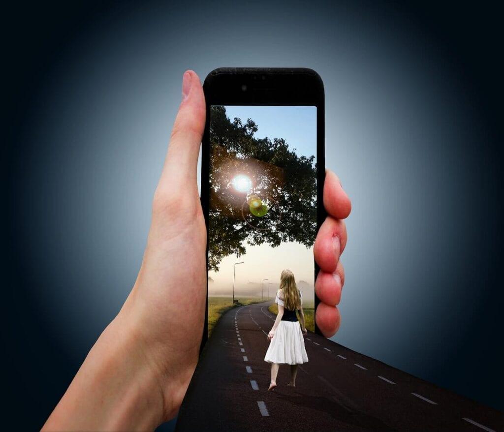 Siyah akıllı telefon ve yolda doğaya yürüyen kız